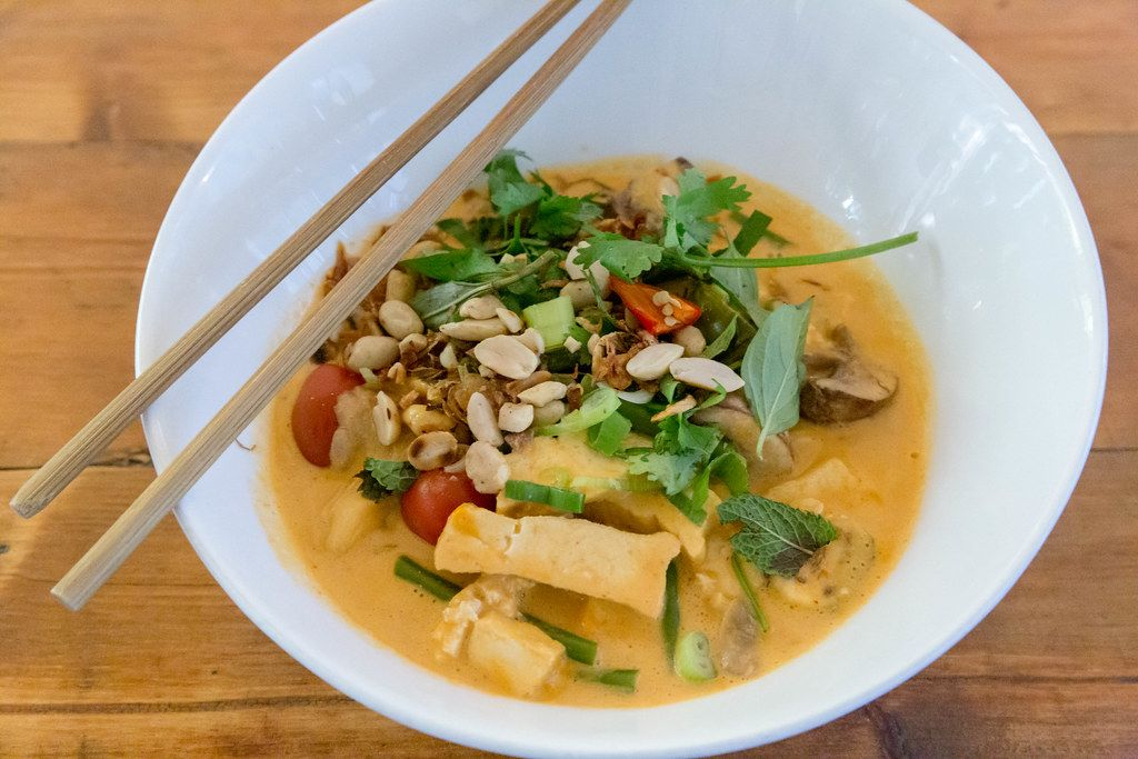 Close-up of Vietnamese meal with chopsticks: Vegan organic tofu in red coconut curry sauce with cherry tomatoes, baby eggplant, fried onions & peanuts