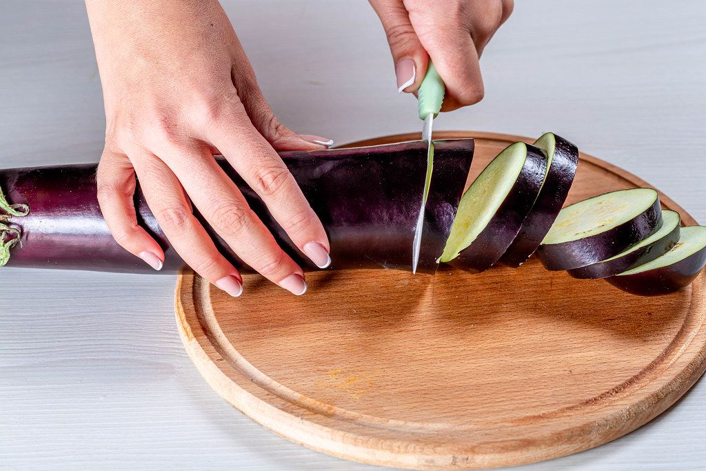 Close-up of woman's hand with knife cuts eggplant (Flip 2019)