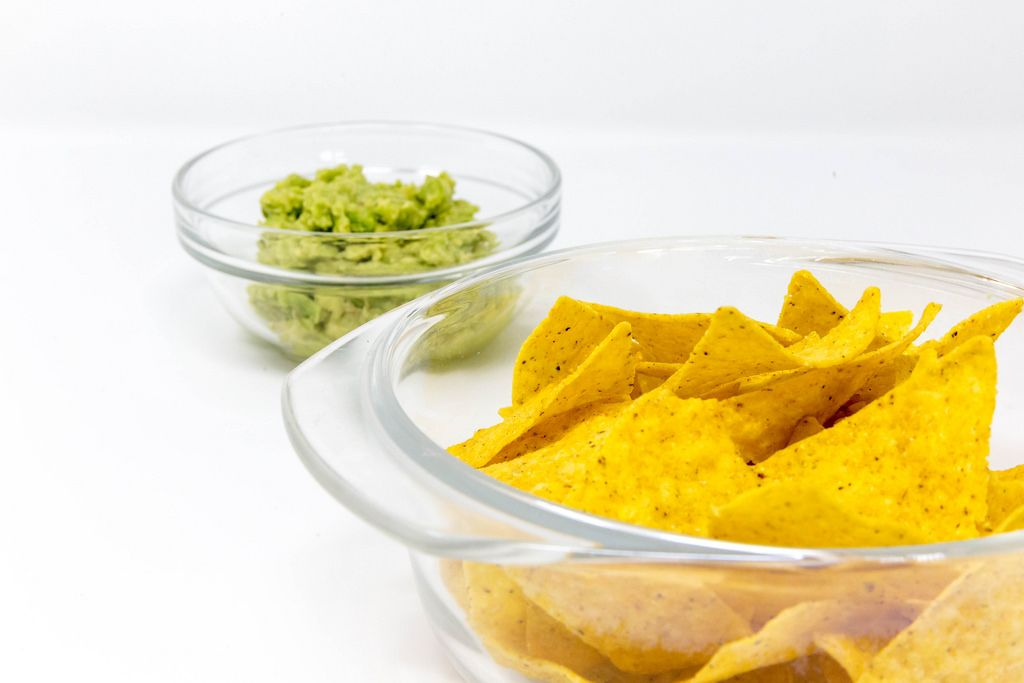 Close Up on Nacho Chips with Guacamole Avocado Dip in the background