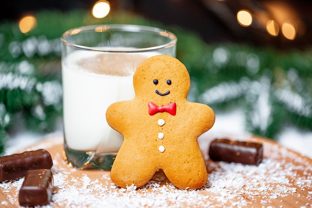 Close Up Photo of a Gingerbread Man leaning on a Glass of Milk with Chocolate Pralines on Christmas Background