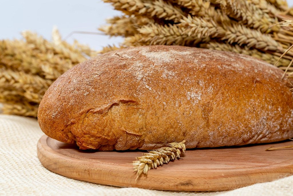 Close Up Photo of a Loaf of Rye Bread on a Wooden Cutting Board with barley spikes