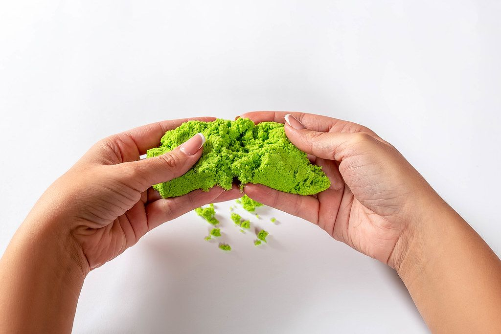 Close Up Photo of a Person holding kinetic sand in both hands on a white background