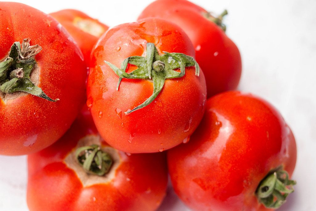 Close Up Photo of Bunch of Washed Red Tomatoes with Water Drops on White Background