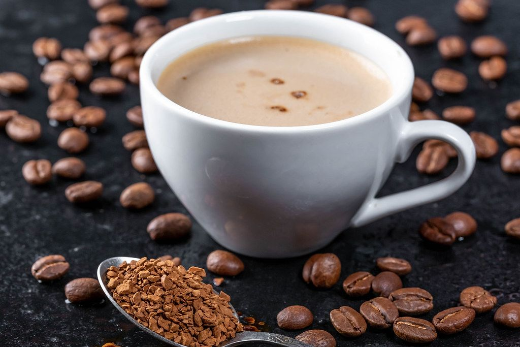 Close Up Photo of Ceramic Cup of Coffee with Roasted Coffee Beans around it on Dark Background