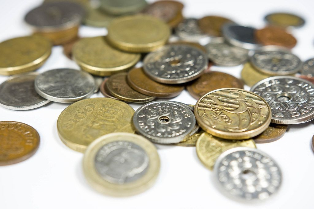Close Up Photo of Coin Collection consisting many different Coins on White Background