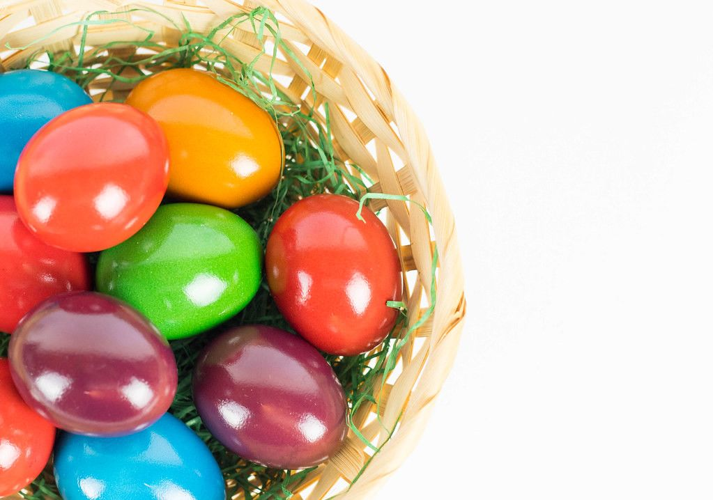 Close Up Photo of Colorful Easter Eggs in a Basket on White Background