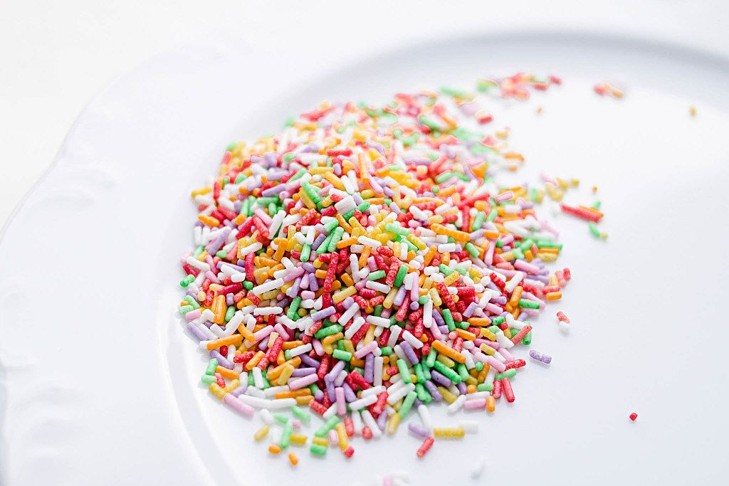 Close Up Photo of Colorful Sprinkles on a White Plate
