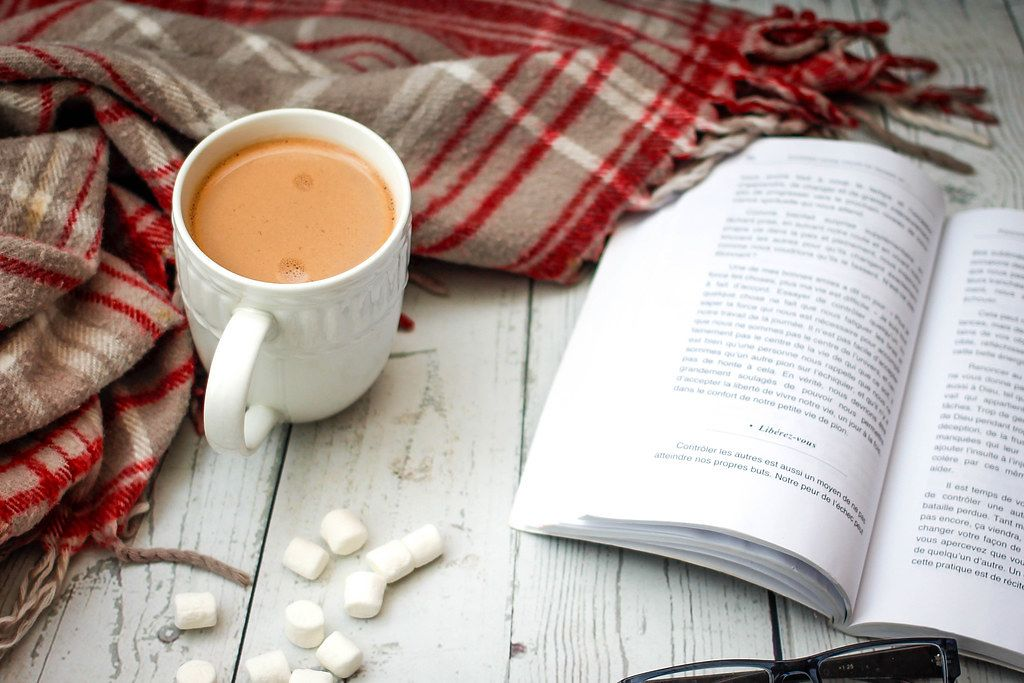 Close Up Photo of Cup of Hot Chocolate standing next to Open Book and Blanket on Wooden Table