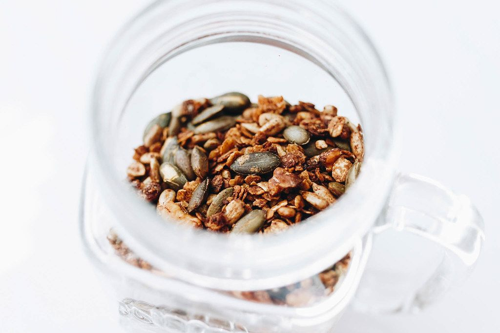 Close Up Photo of Homemade Granola with Nuts in a Glass on White Background