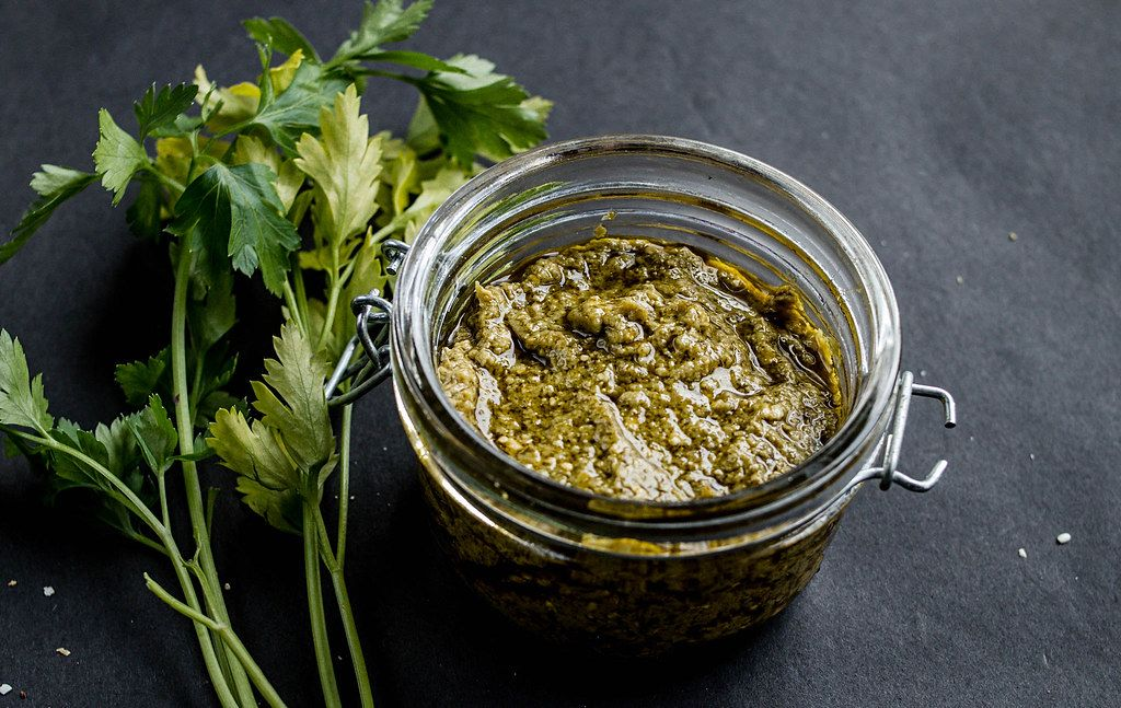 Close Up Photo of Homemade Green Pesto in a Glass Jar with Parsley on Dark Background