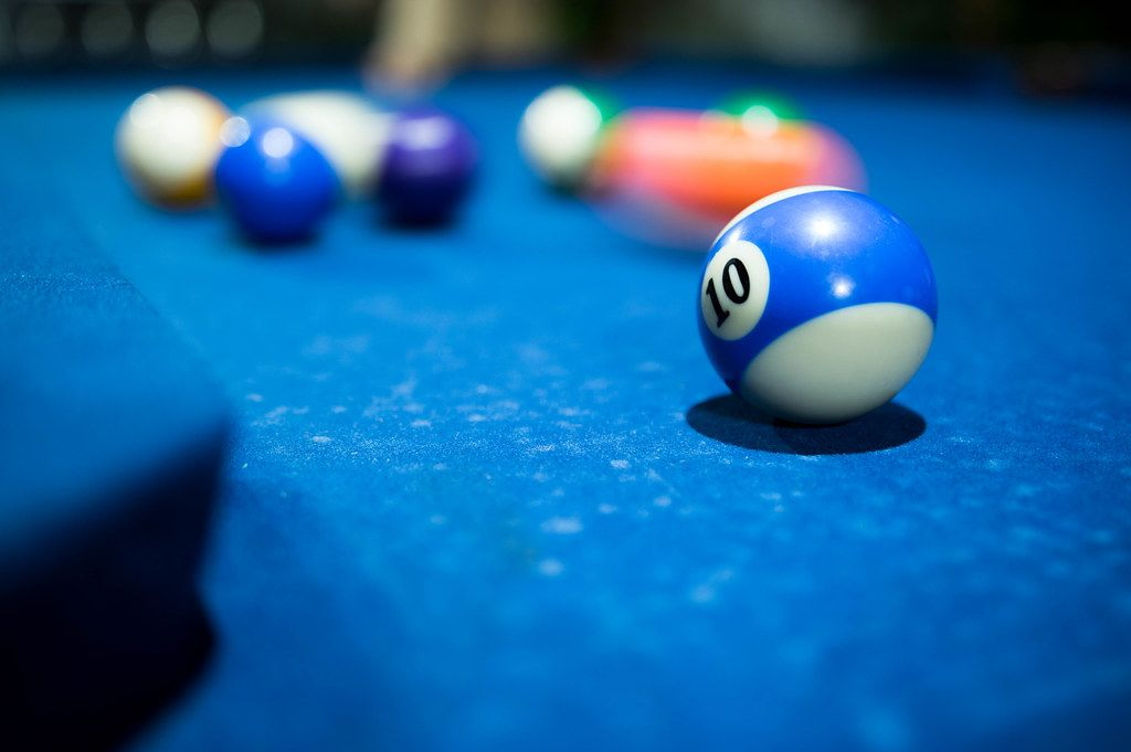 Close Up Photo of Number 10 Pool Ball on a Blue Pool Table with other Pool Balls in the Background