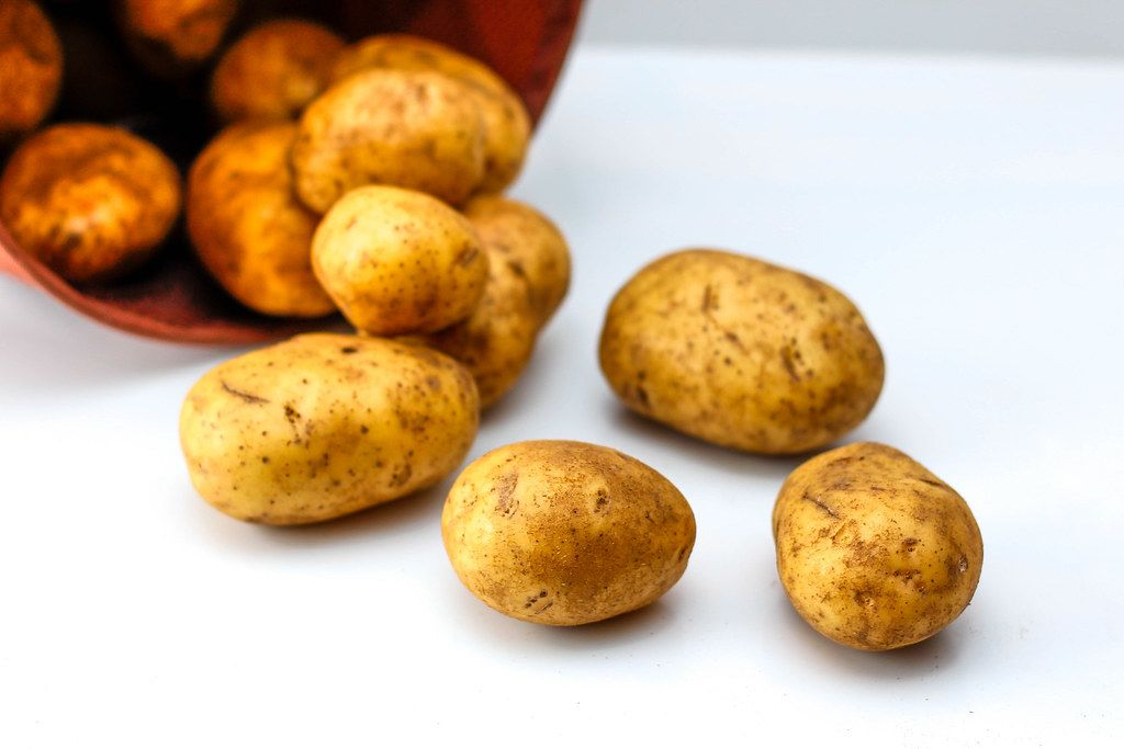 Close Up Photo of Potatoes falling out of a Bowl on white Background