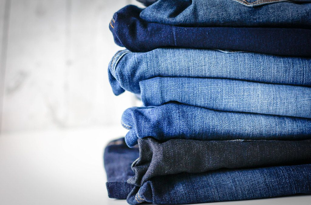 Close Up Photo of Stack of different colored Jeans with white Background