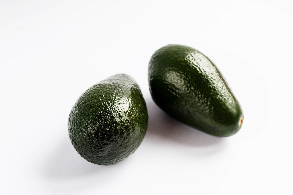Close Up Photo of Two Avocados on white Background