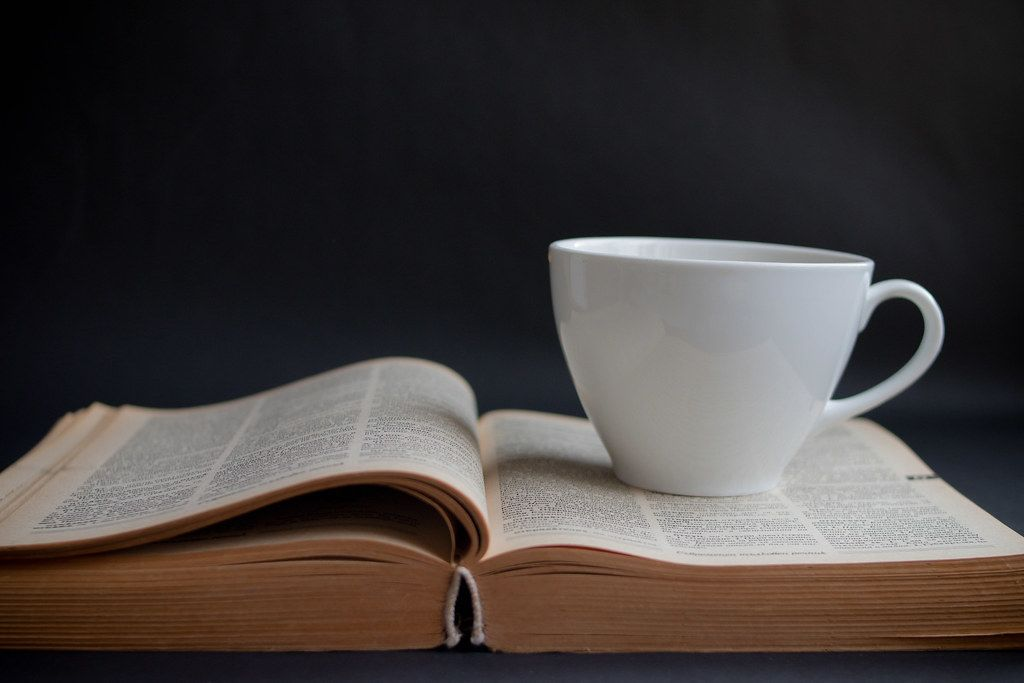 Close Up Photo of White Coffee Cup on open Book on Black Background