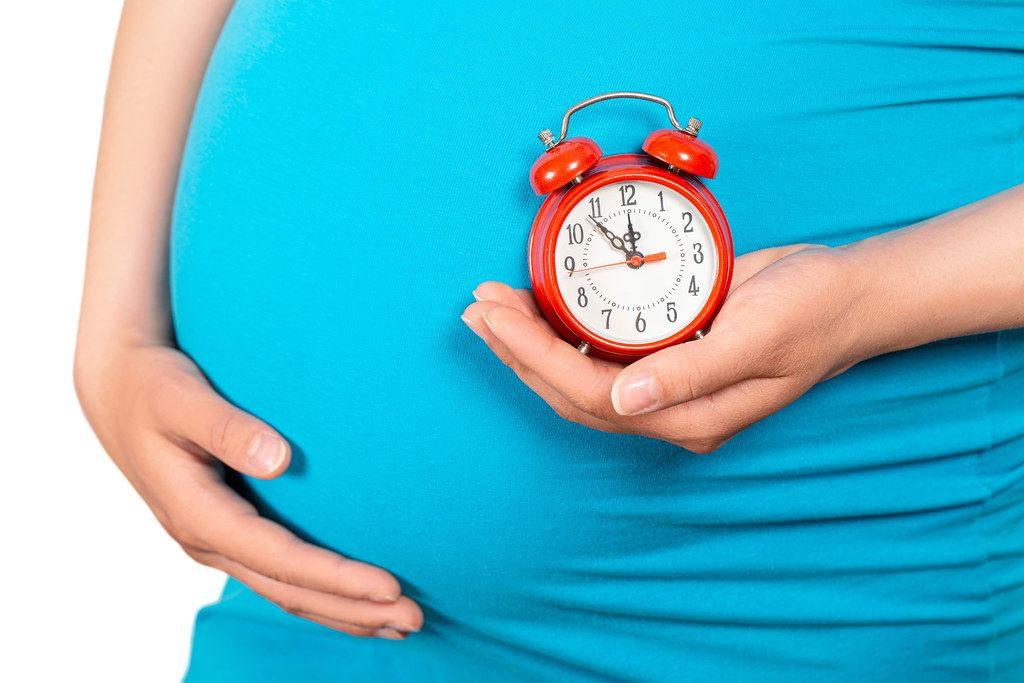 Close up, pregnant belly and alarm clock. Baby birth forthcoming concept