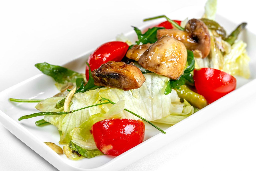 Close - up salad with fresh vegetables and pieces of mushrooms