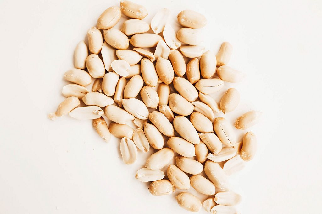 Close up top view of raw peanuts on white background