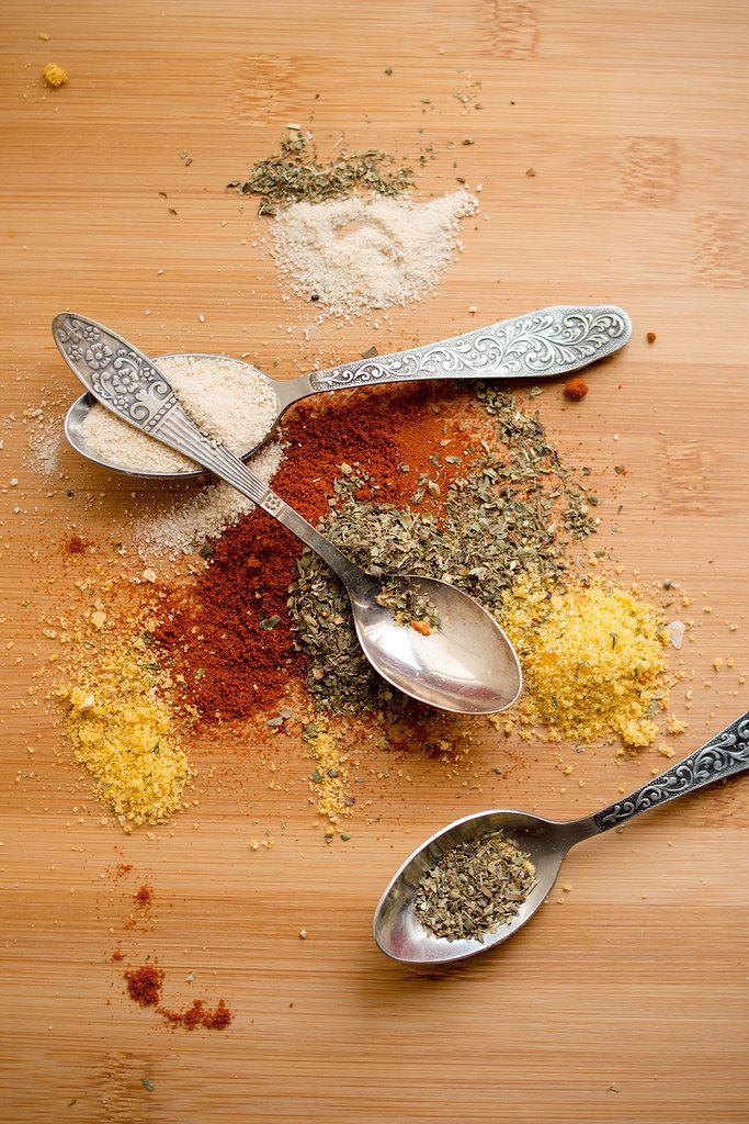 Close Up Top View Photo of Different Spices with three Spoons on Wooden Table