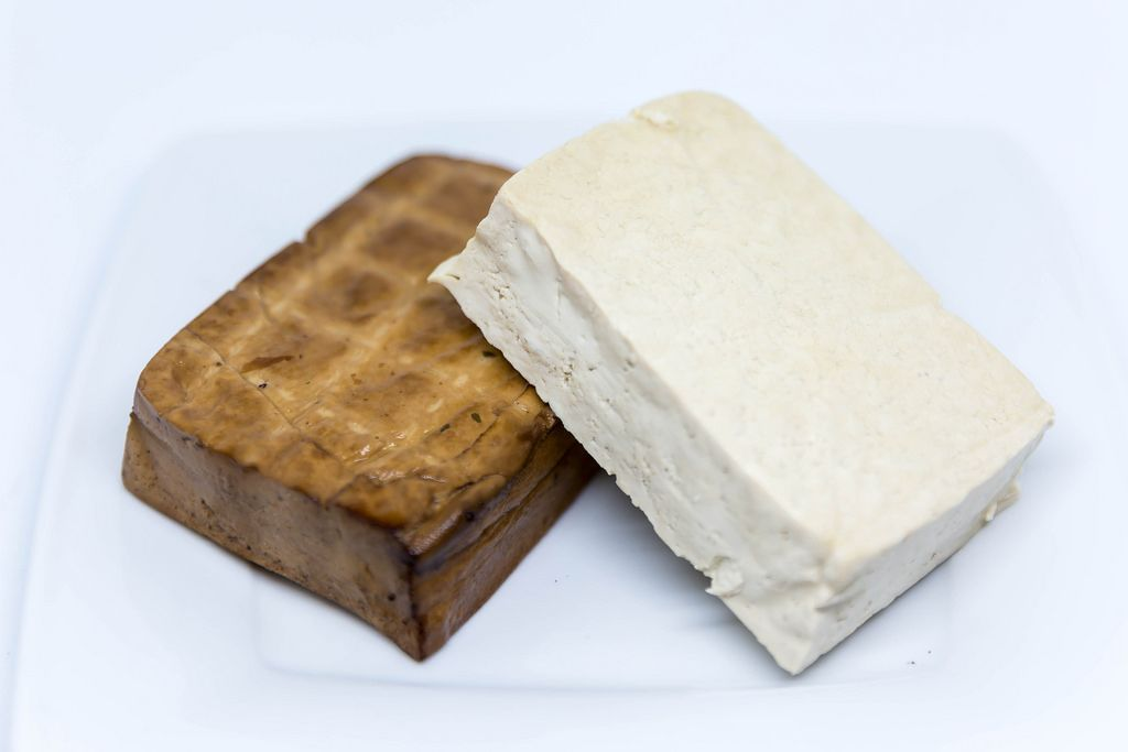 Close-up view of tofu and smoked tofu on a white plate