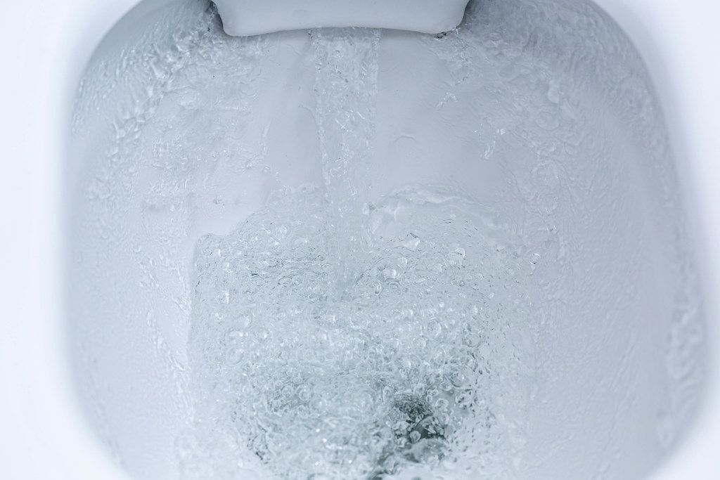 Closeup view of a flushing white toilet. The water swirls in the toilet bowl