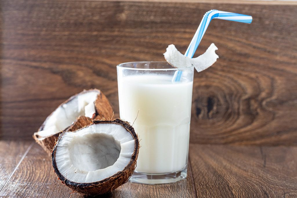 Coconut halves with a glass of coconut milk on a brown wooden background
