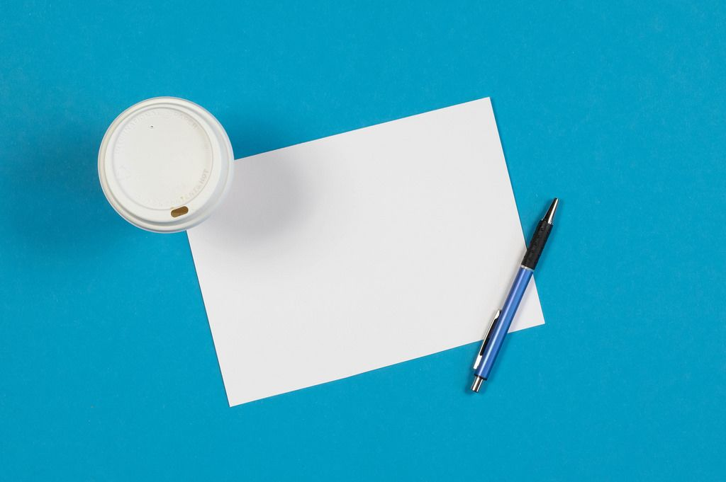 Coffee and blank paper on blue background