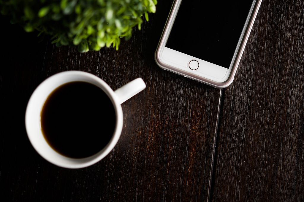 Coffee cup and phone on a wooden table