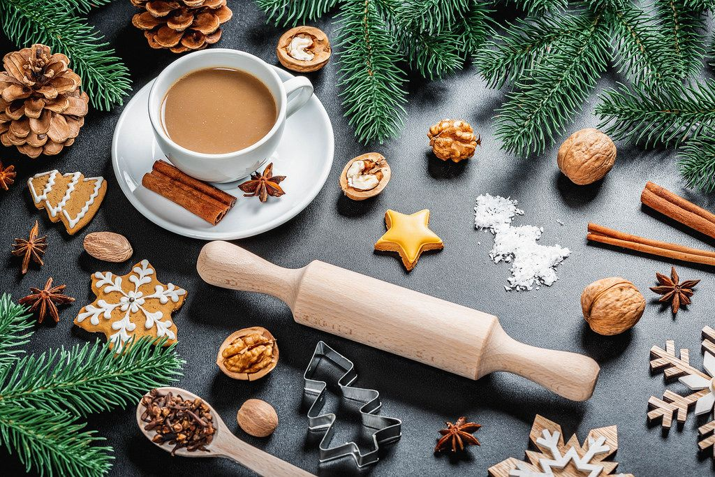 Coffee with anise and cinnamon on a New Year's background with a rolling pin, Christmas tree branches, gingerbread and cones