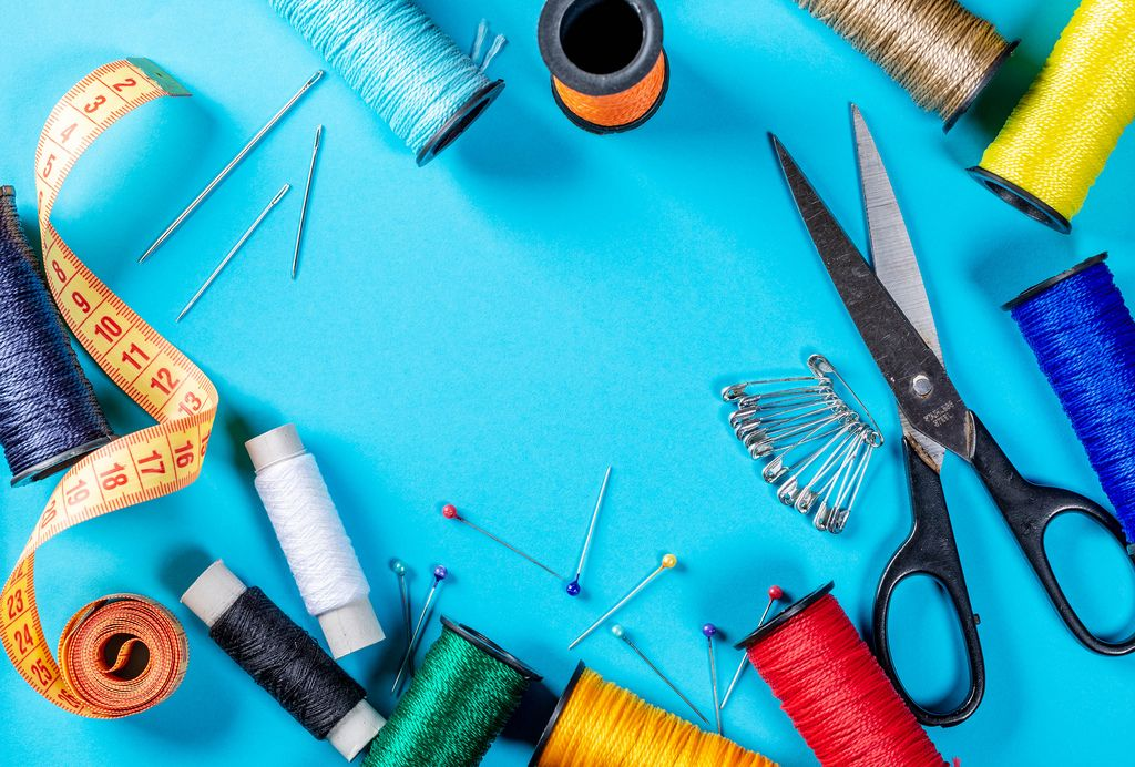 Collection of attributes for embroidery and sewing on blue background