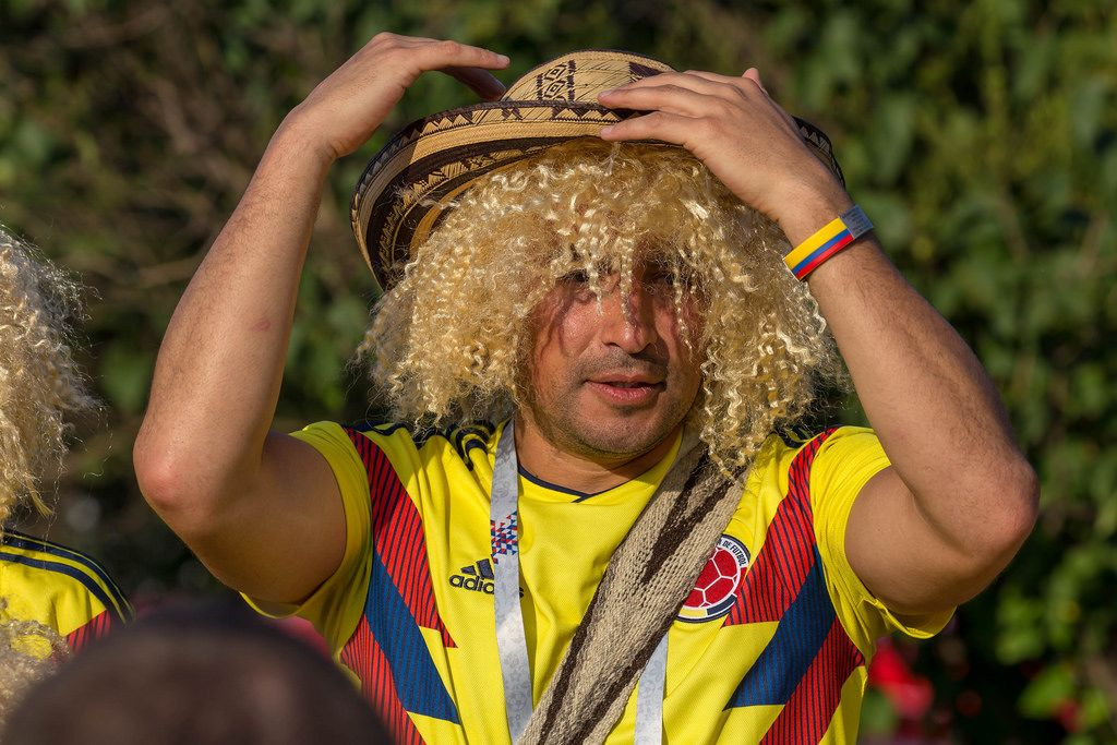 Colombian soccer fan with blonde wig and straw hat