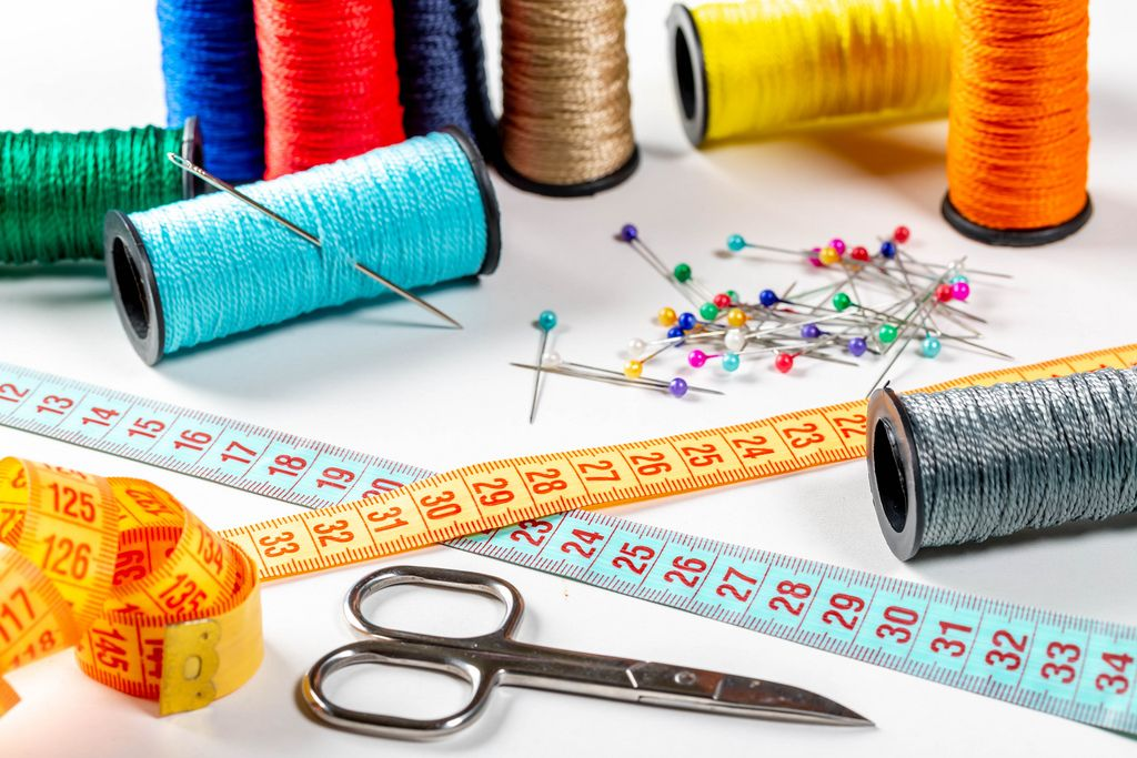 Colored sewing thread and bobbin with measuring tape, scissors and needles