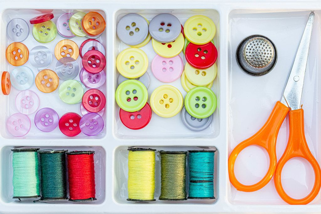 Colorful buttons, thread with scissors and thimble in a sewing box
