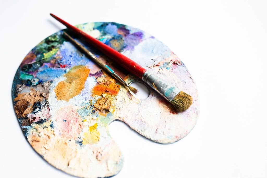 Colourful painter's palette with oil paint and brushes on white background