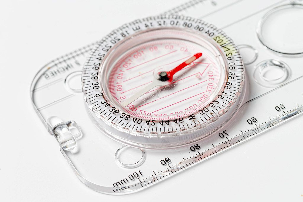 Compact compass with ruler on white background close-up (Flip 2020)