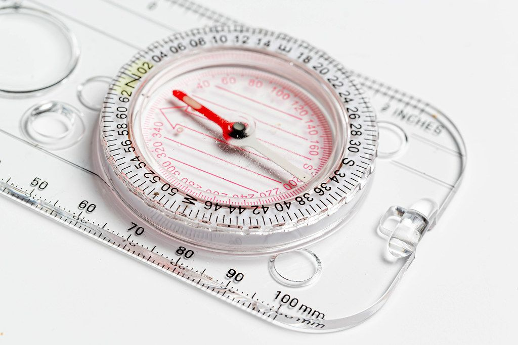 Compact compass with ruler on white background close-up