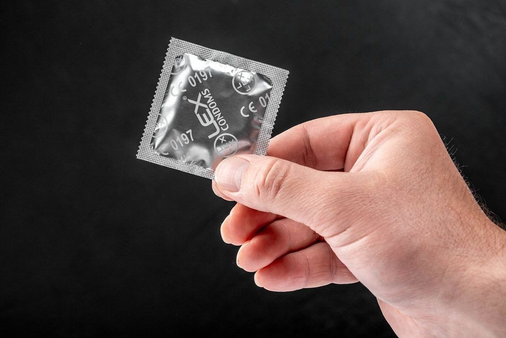 Condom in the hand of a man on a black background. The concept of individual protection