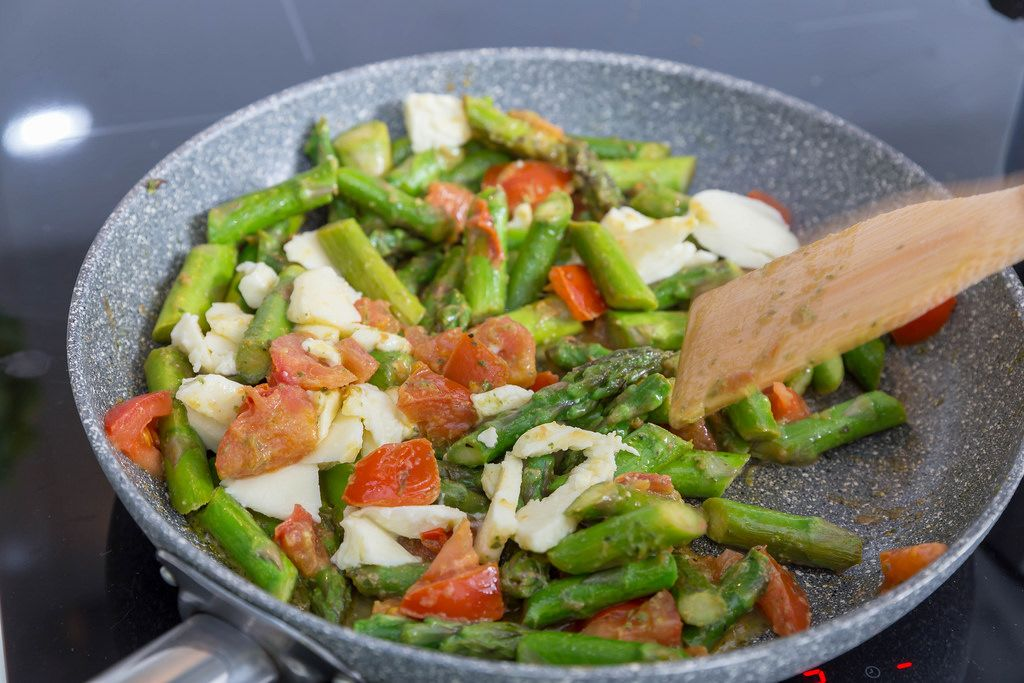 Cooking green asparagus with penne pasta, tomato and mozzarella