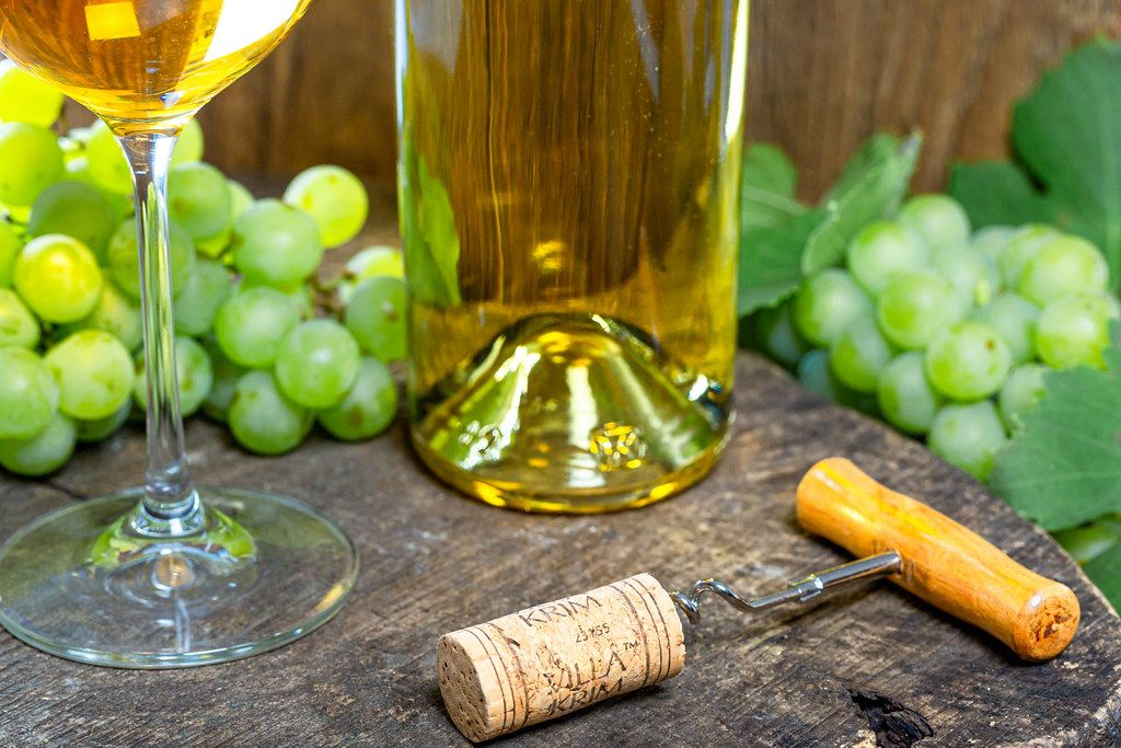 Corkscrew with a crust on the background of a bottle of white wine and grapes