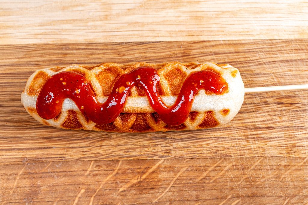 Corn dog with ketchup on wooden background