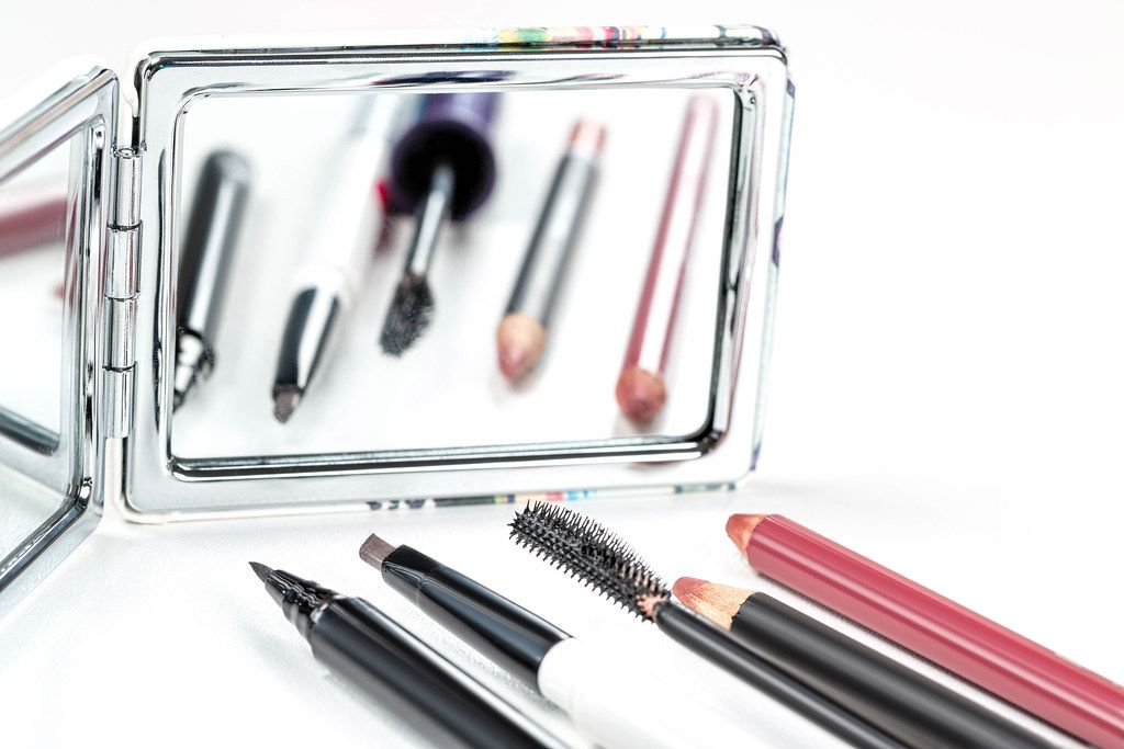 Cosmetic pencils, eyeliner and carcasses on the background of a mirror