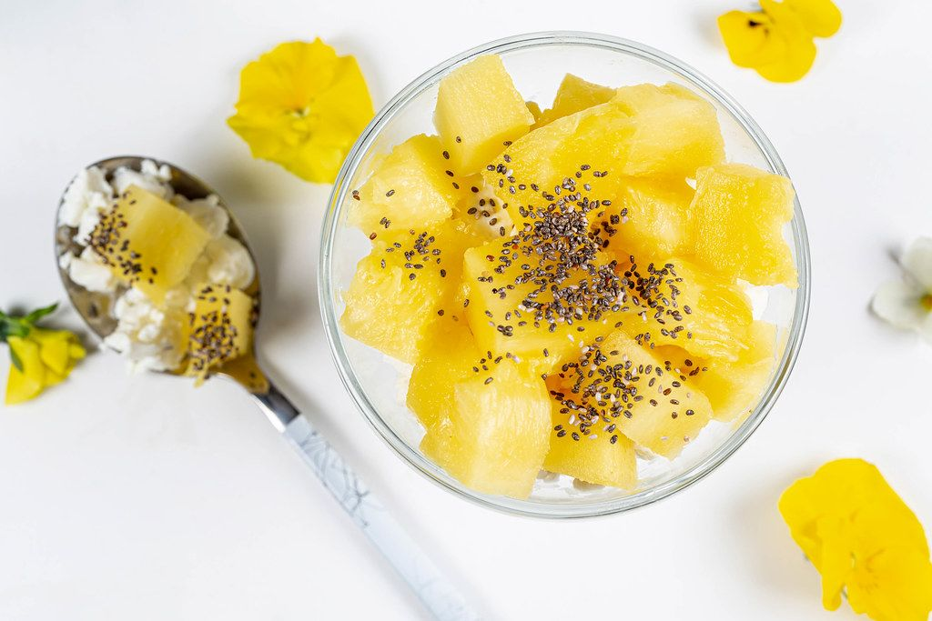 Cottage cheese with pineapple slices and Chia seeds on a white background, top view