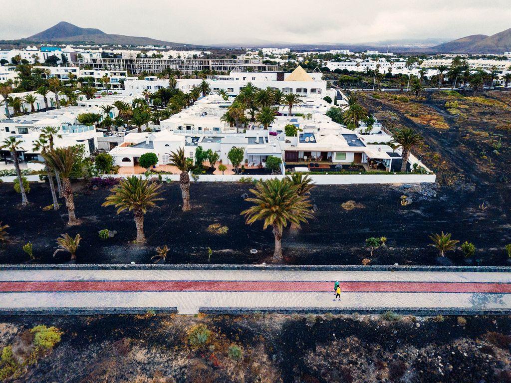 Couple walking beside the resort city in Canary Islands / Paare, die neben der Urlaubsstadt in Kanarischen Inseln gehen