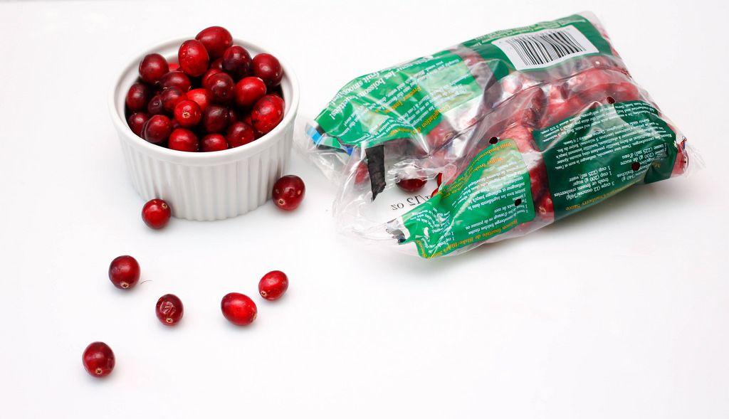 Cranberrys in der Verpackung und Schüssel vor weißem Hintergrund