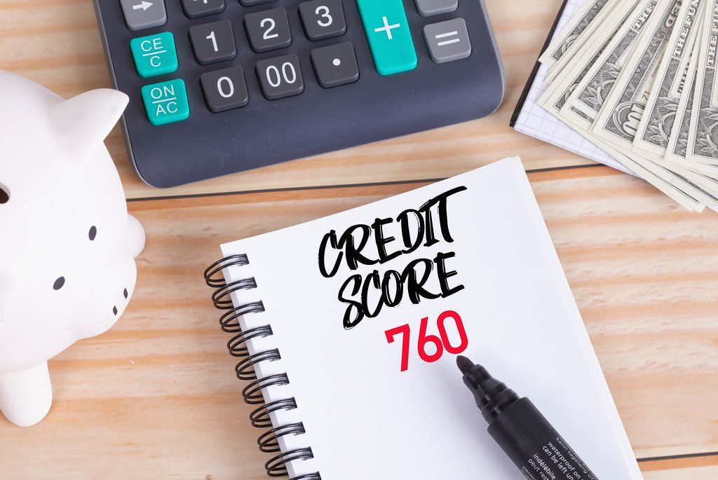 Credit score 760 text in notebook with piggy bank and calculator on wooden table