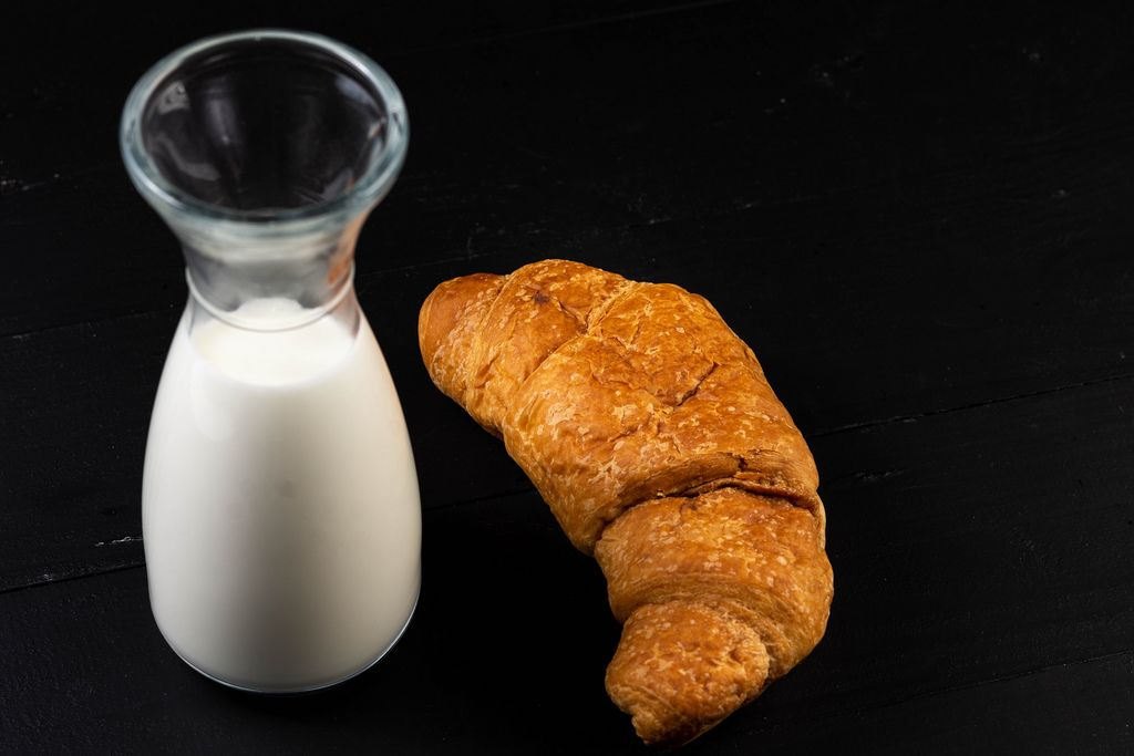 Croissant with milk on the black board