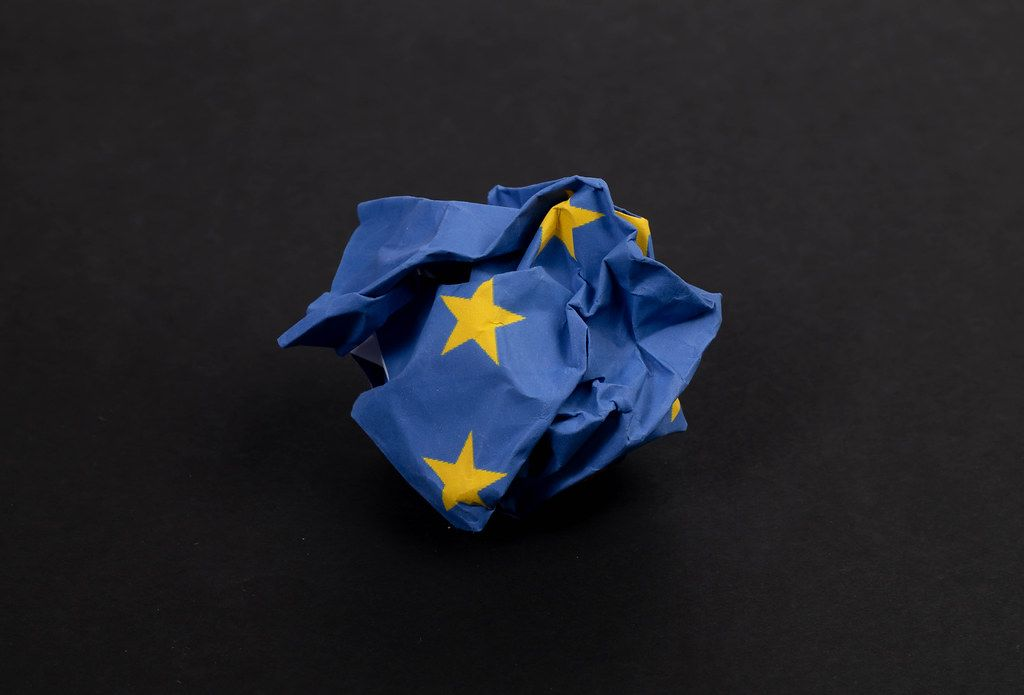 Crumbled paper in blue with stars as the European flag symbolising the critical situation for Europe