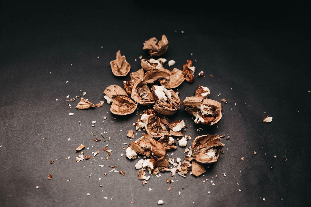 Crushed walnuts on black background.