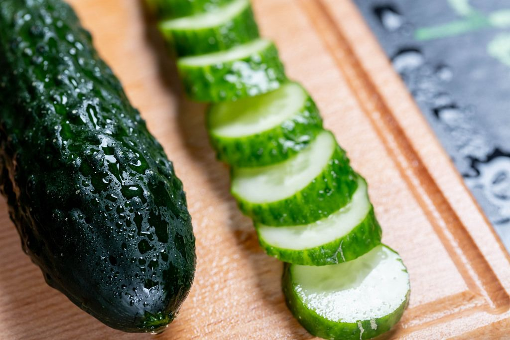 Cucumber sliced on a wooden board.