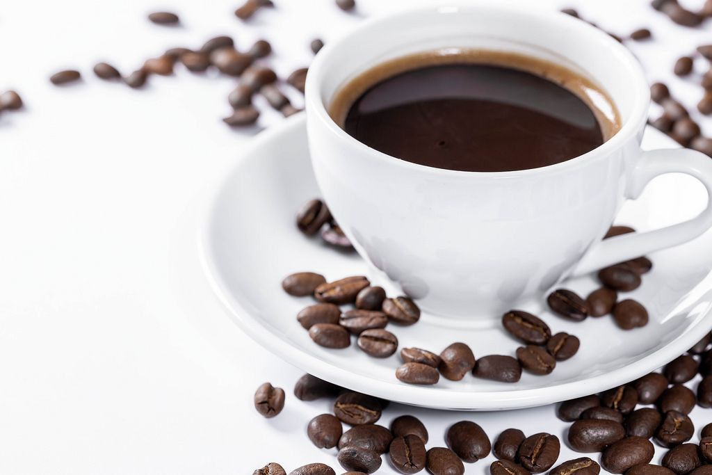 Cup of hot fresh coffee on a white background with grains
